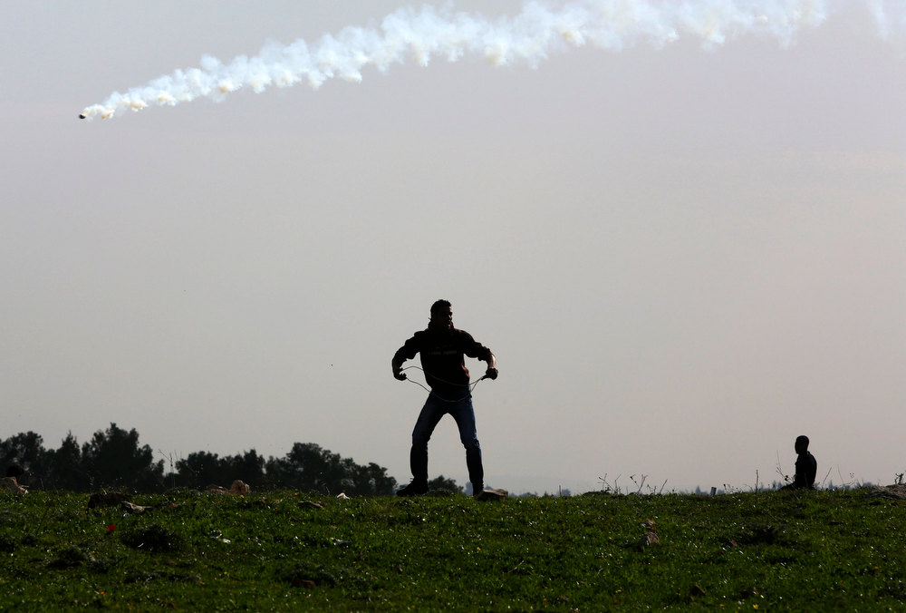 . A Palestinian protester holds a sling as a tear gas canister fired by Israeli security forces flies overhead during clashes at a protest against the controversial Israeli barrier, in the West Bank village of Budrus near Ramallah January 25, 2013. REUTERS/Mohamad Torokman