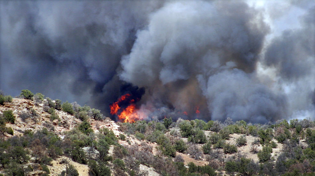 . Black smoke billows above flames near the south rim entrance to the Royal Gorge Bridge at County Road 3 in western Fremont County Tuesday afternoon, June 11, 2013 west of Canon City, Colo. The fire was one of several that started across the state in the midst of recording-setting hot temperatures and high winds. (AP Photo/The Pueblo Chieftain, Tracy Harmon)