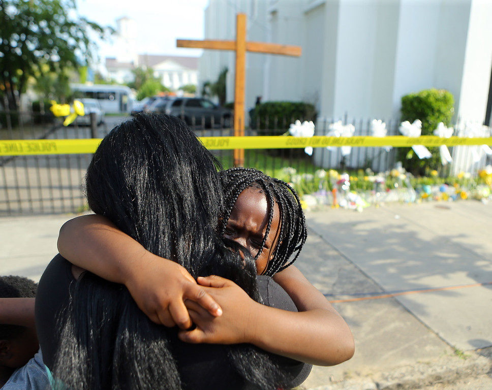 . Kearston Farr hugs her 5-year-old daughter Taliyah visiting a memorial in front of the Emanuel AME Church on Friday, June 19, 2015 in Charleston, S.C.  Dylann Storm Roof, 21, is accused of killing nine people during a Wednesday night Bible study at the church.   ( Curtis Compton/Atlanta Journal-Constitution via AP)