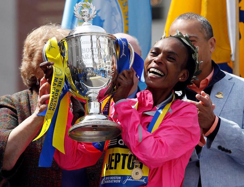 . The 117th Boston Marathon women\'s division winner Rita Jeptoo of Kenya reacts as she is handed the Boston Marathon trophy in Boston, Massachusetts April 15, 2013. REUTERS/Jessica Rinaldi