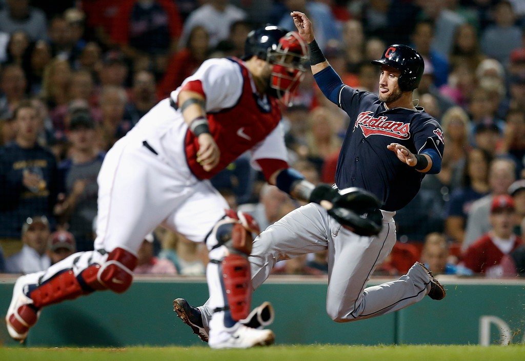 . Cleveland Indians\' Yan Gomes, right, scores behind Boston Red Sox\'s Sandy Leon on a single by Michael Brantley during the sixth inning of a baseball game in Boston, Tuesday, Aug. 21, 2018. (AP Photo/Michael Dwyer)