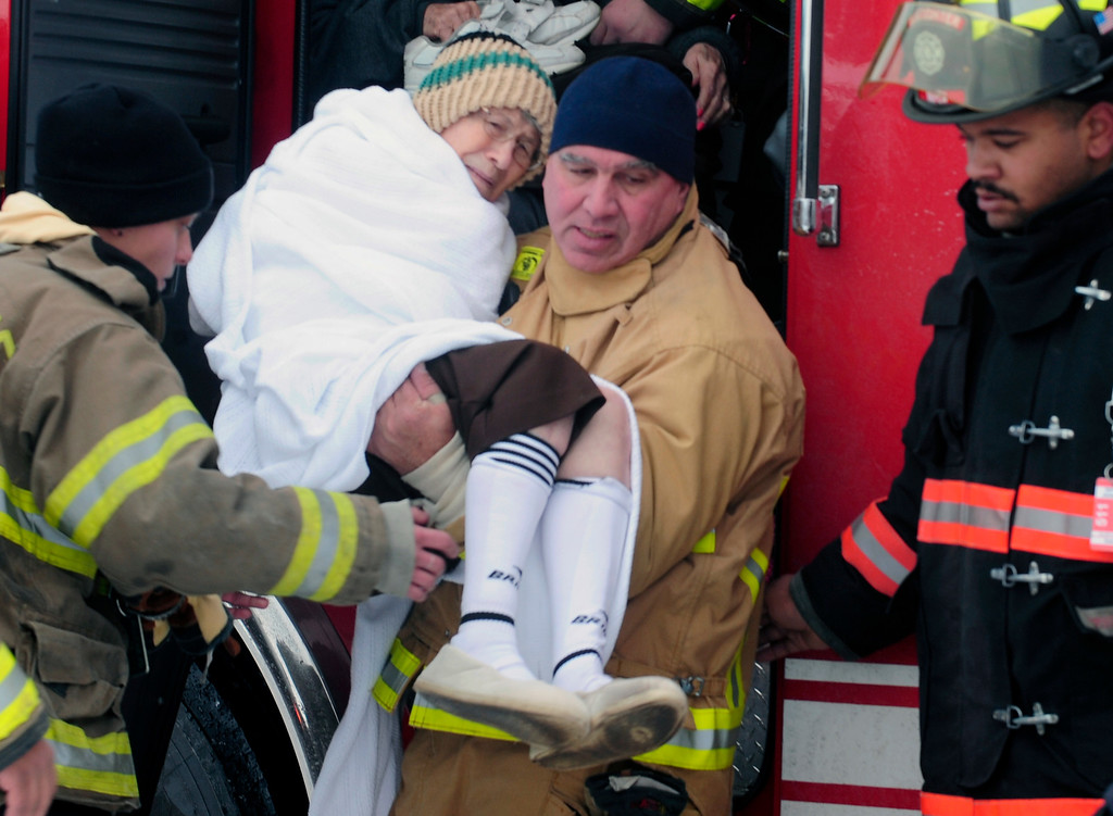 . Firefighters from Cheektowaga and Depew  carry a patient from from Garden Gate Health Care Facility to the Appletree Mall in Cheektowaga, N.Y.,  Thursday, Nov. 20, 2014. About 180 patients from the facility were moved after officials questioned sustainability of the the roof from the  snowfall.   Roofs began to creak and collapse under the weight of excessive snow as another storm Thursday added to epic snowfall in western New York state. (AP Photo/Gary Wiepert)