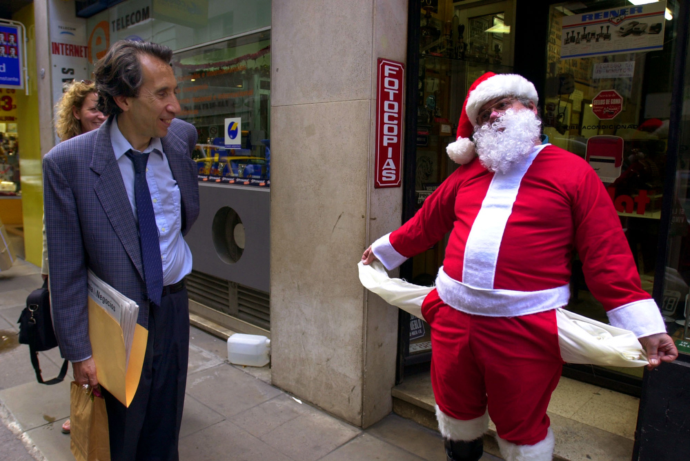 Description of . Roberto Schettini, dressed as Santa Claus, shows his empty pockets, Friday, Dec. 21, 2001, in Buenos Aires. A $132 billion debt crisis and four years of recession have left Argentina teetering on the edge of financial collapse and close to defaulting on its crushing debt burden. Many economists predict a default or a devaluation are now imminent as the economy shows few signs of regaining strength.(AP Photo/Walter Astrada)