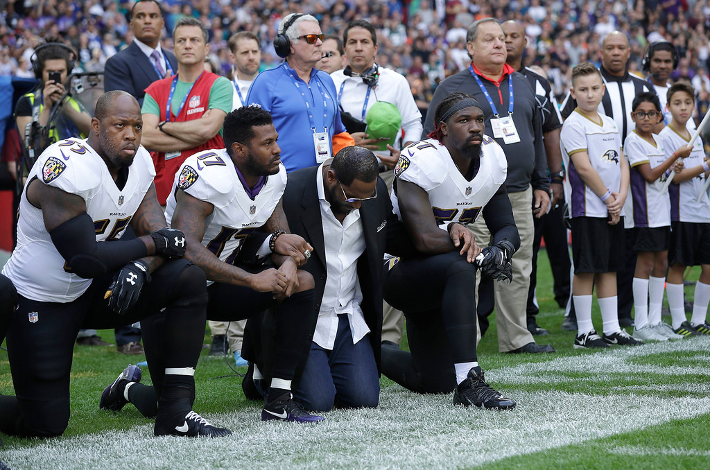 . Baltimore Ravens outside linebacker Terrell Suggs, from left, Mike Wallace, former player Ray Lewis and inside linebacker C.J. Mosley kneel down during the playing of the U.S. national anthem before an NFL football game between the Jacksonville Jaguars and the Ravens at Wembley Stadium in London, Sunday Sept. 24, 2017. (AP Photo/Matt Dunham)