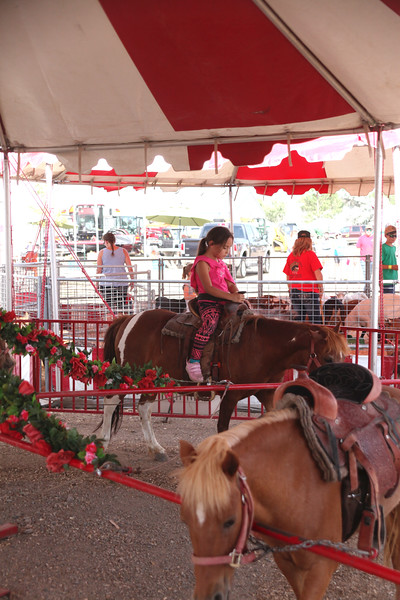 Havre Daily News / Floyd Brandt   Carlie Collins enjoys a pony ride on the Midway at the Blain County Fair Saturday.