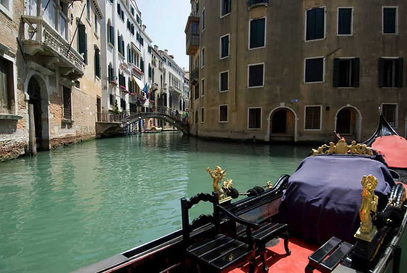 View of small bridge over narrow canal from gondola in Venice, Italy