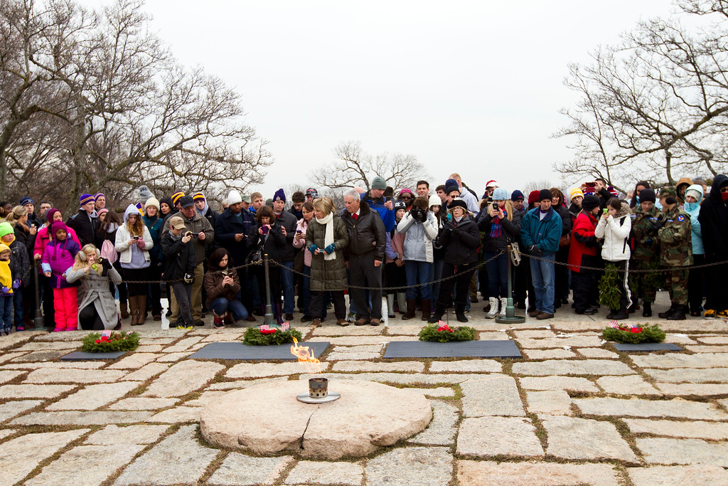 . Visitors look the holiday wreaths at the gravesite of President John F. Kennedy at Arlington National Cemetery in Arlington, Va., Saturday Dec. 14, 2013, during Wreaths Across America Day. Wreaths Across America was started in 1992 at Arlington National Cemetery by Maine businessman Morrill Worcester and has expanded to hundreds of veterans\' cemeteries and other locations in all 50 states and beyond. (AP Photo/Jose Luis Magana)