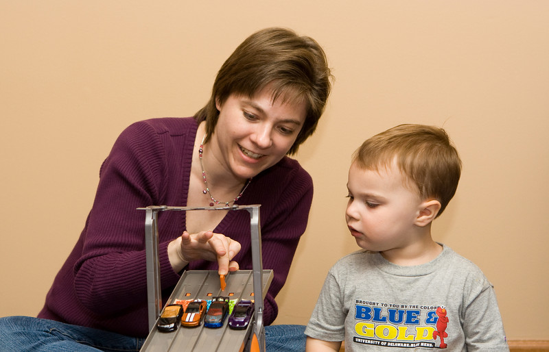K.C. learns from Mom how to launch cars on his new race track.