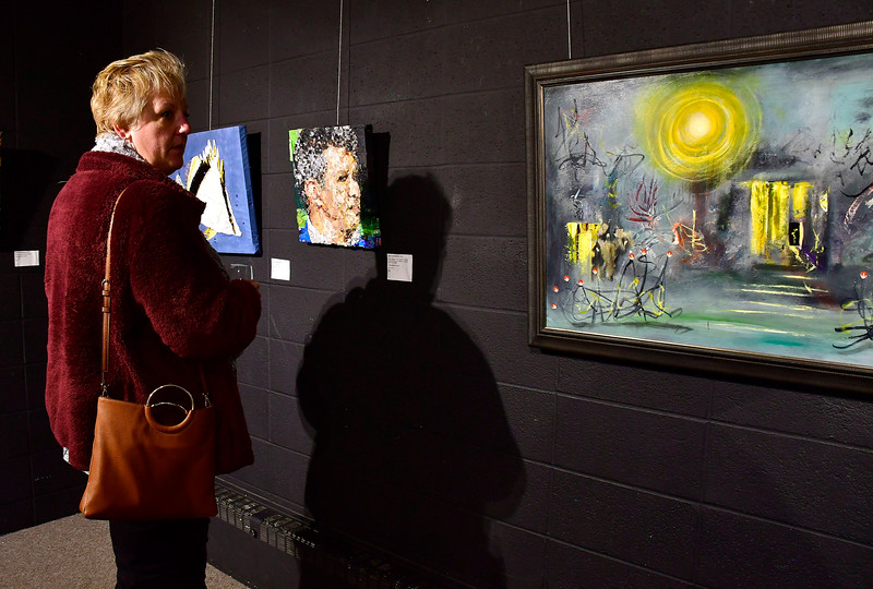 1/10/2019 Mike Orazzi | Staff Joann Cooley looks over art on display during the Greater New Britain Arts Alliance Artist Members Show held at the Stockman Gallery in downtown New Britain Thursday night.
