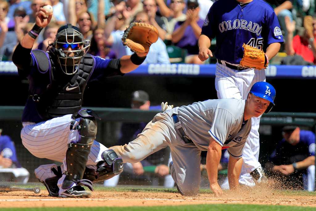 . Los Angeles Dodgers\' Mark Ellis, right, is tagged out by Colorado Rockies\' Yorvit Torrealba, left, after trying to score from second on a Jerry Hairston single during the third inning of a baseball game Saturday June 1, 2013 in Denver. Scott Van Slyke scored on the play. (AP Photo/Barry Gutierrez)