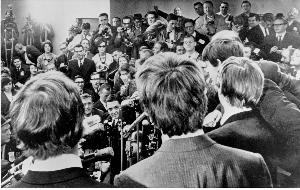 . The Beatles face the media on arrival at JFK airport in New York City on Feb. 7, 1964. The British rock and roll group was also greeted by a screaming crowd estimated at 5,000. (AP Photo/Charles Tasnadi)