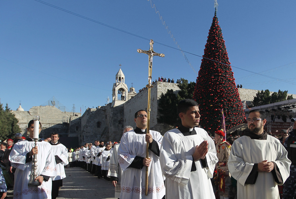 """. A clergyman holds a crucifix in Manger Square outside the Church of the Nativity as Christians gather for Christmas celebrations in the West Bank city of Bethlehem, on December 24, 2013. Thousands of Palestinians and tourists flocked into the West Bank city of Bethlehem to mark Christmas in the \""""little town\"""" where many believe Jesus Christ was born.  MUSA AL-SHAER/AFP/Getty Images"""