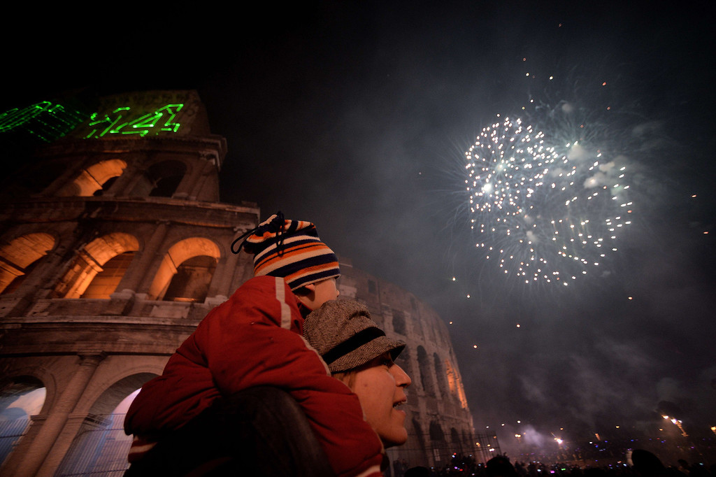 . People celebrate the new year by the ancient Coliseum in Rome on January 1, 2014. FILIPPO MONTEFORTE/AFP/Getty Images