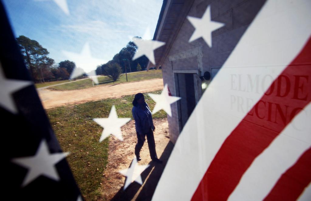 . Barbara Hawkins is seen through an American flag as she walks into the Elmodel precinct to cast her ballot, Tuesday, Nov. 4, 2014, in Elmodel, Ga. (AP Photo/David Goldman)