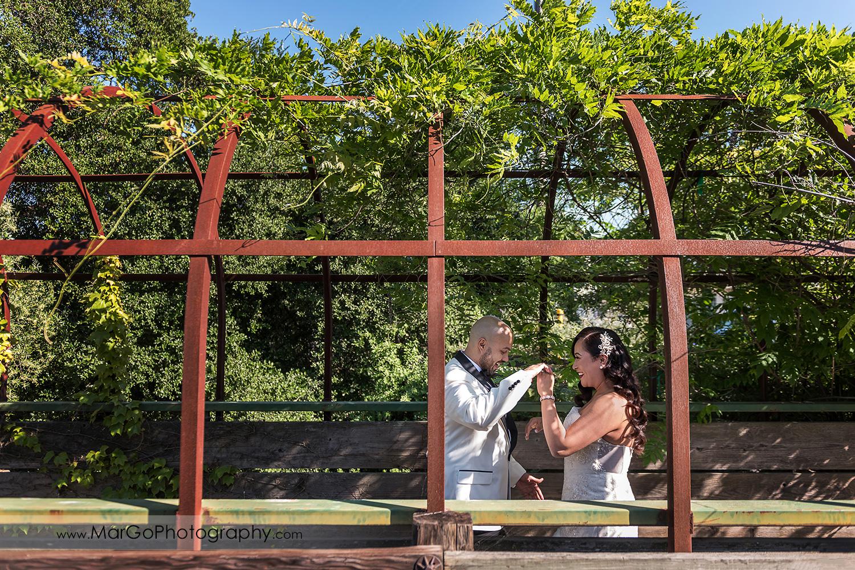 groom admiring bride in green tunnel near Sunol's Casa Bella