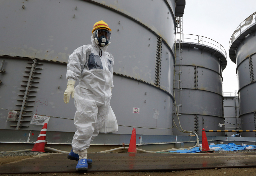 . A Tokyo Electric Power Co. employee wearing a protective suit and a mask walks past storage tanks for radioactive water in the H4 area at the Fukushima Dai-ichi nuclear power plant in Okuma, Fukushima, northeastern Japan, Thursday, Nov. 7, 2013.  (AP Photo/Tomohiro Ohsumi, Pool)