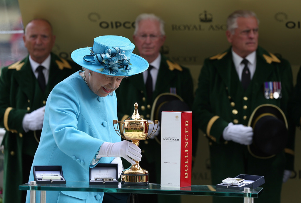 . Queen Elizabeth II picks up the Gold Cup to present it to the connections of Leading Light after the Gold Cup on day three of Royal Ascot at Ascot Racecourse on June 19, 2014 in Ascot, England. (Photo by Steve Bardens/Getty Images)