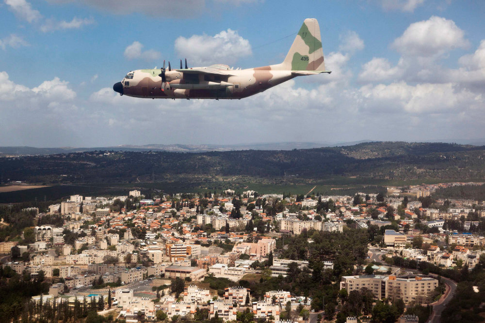. An Israel Air Force C-130 Hercules plane flies over the northern Israeli village of Tirat Ha\'Carmel, as part of an aerial show for Israel\'s Independence Day, marking the 65th anniversary of the creation of the state, April 16, 2013. REUTERS/ Nir Elias