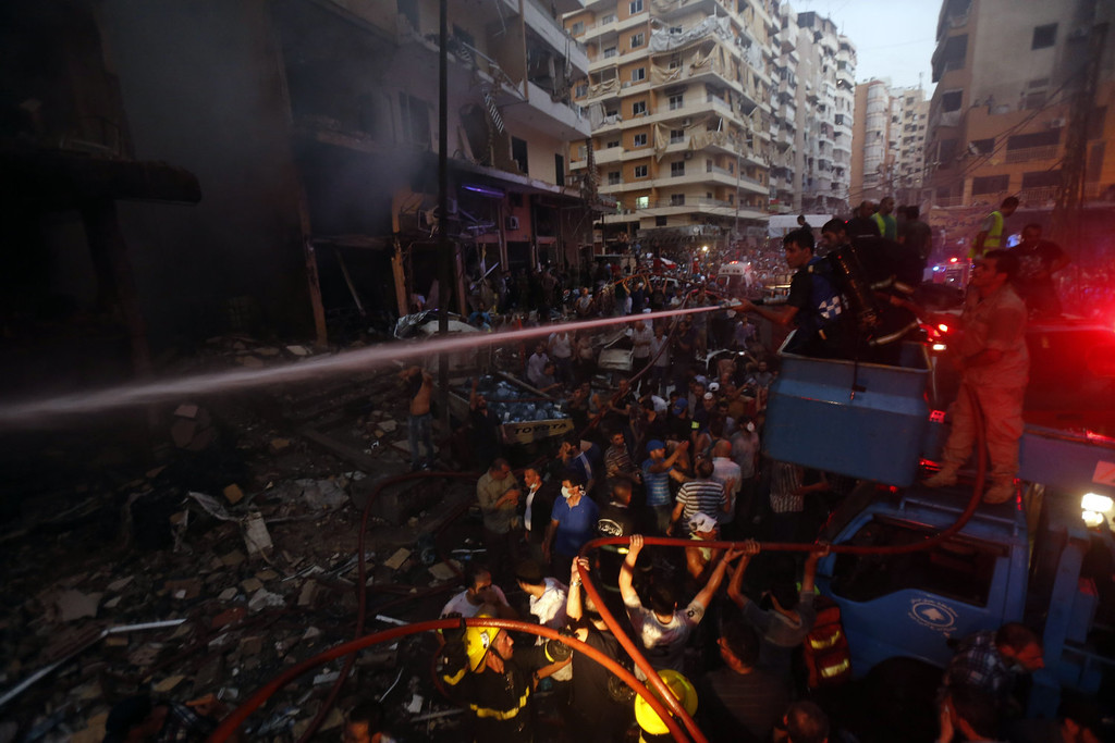 . Lebanese fire fighters extinguish a flame at the site of a car bomb between the Bir el-Abed and Roueiss neighborhoods, in the southern suburb of Beirut on August 15, 2013. A powerful car bomb killed at least six people and more than 100 wounded in a Beirut stronghold of Shiite movement Hezbollah, an army source and Lebanese Red Cross said.   STR-/AFP/Getty Images