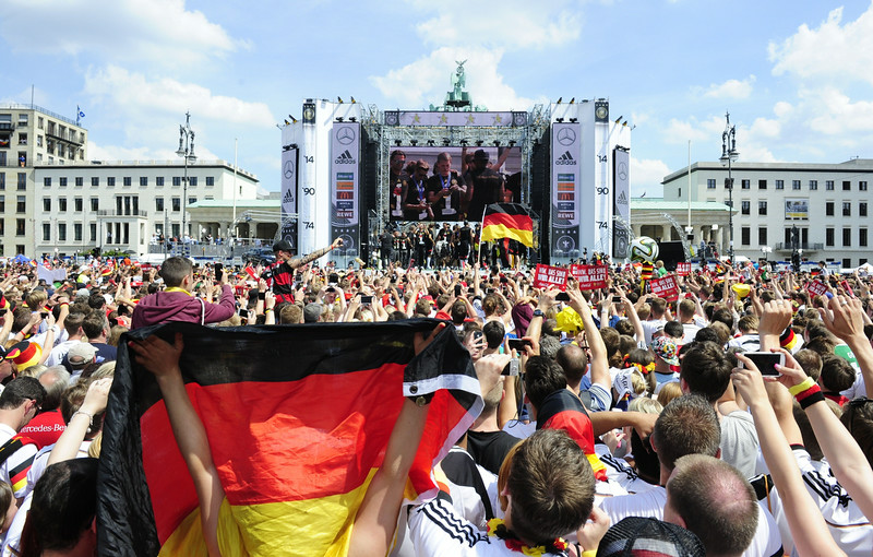 . Fans cheer as image of German football players is seen on a giant screen during celebrations of the German national team at Berlin\'s landmark Brandenburg Gate to celebrate their FIFA World Cup title on July 15, 2014. Germany won their fourth World Cup title, after 1-0 win over Argentina on July 13, 2014 in Rio de Janeiro in the FIFA World Cup Brazil final game. (ROBERT MICHAEL/AFP/Getty Images)