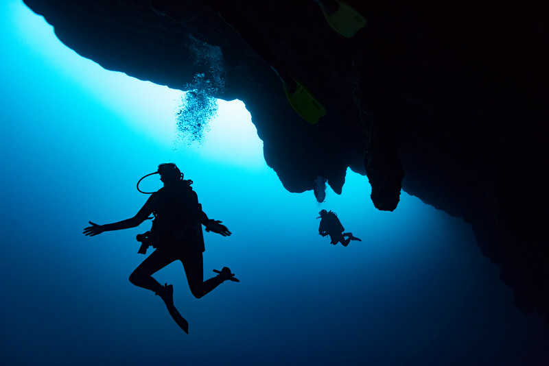 Silhouette of scuba divers, The Great Blue Hole, Belize Barrier Reef, Lighthouse Reef, Belize