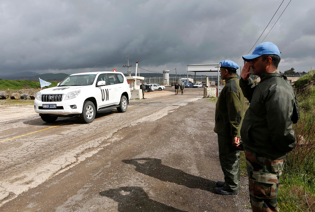 . India\'s United Nations peacekeepers salute as a U.N. vehicle crosses from Syria into Israel at the Kuneitra border crossing on the Golan Heights March 5, 2013. Syrian rebels have seized a convoy of U.N. peacekeepers near the Golan Heights and say they will hold them captive until President Bashar al-Assad\'s forces pull back from a rebel-held village which has seen heavy recent fighting. Israel captured the Golan Heights in the 1967 Middle East war and annexed it in 1981 in a move not recognized internationally. Picture taken March 5, 2013. REUTERS/Baz Ratner