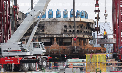 Bertha's massive cutter head is suspended face down as it is hoisted to the surface of its access pit next to the Alaskan Way Viaduct in Seattle, Washington