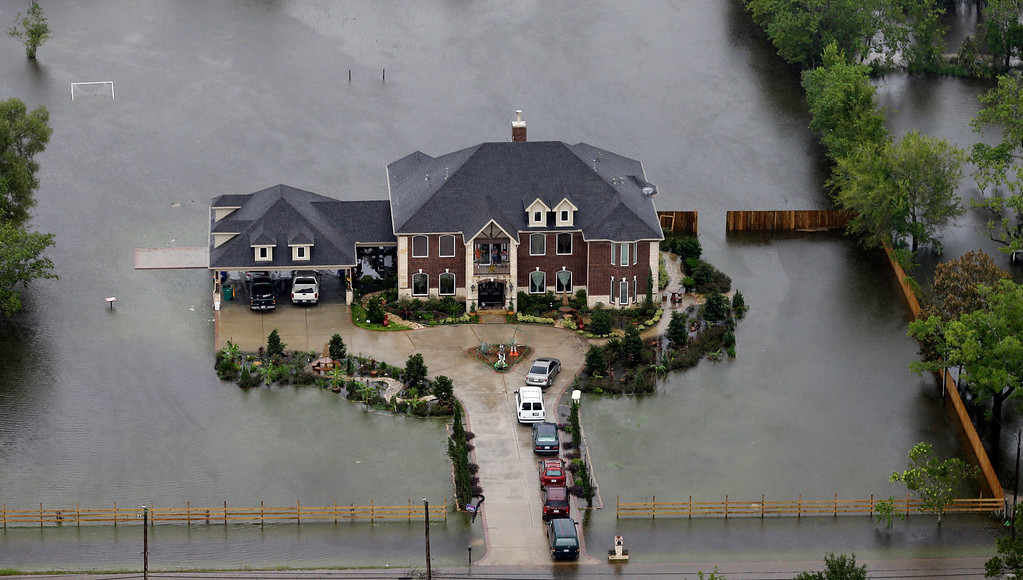 . A home is surrounded by floodwaters from Tropical Storm Harvey on Tuesday, Aug. 29, 2017, in Houston. With its flood defenses strained, the crippled city of Houston anxiously watched dams and levees Tuesday to see if they would hold until the rain stops, and meteorologists offered the first reason for hope � a forecast with less than an inch of rain and even a chance for sunshine. (AP Photo/David J. Phillip)