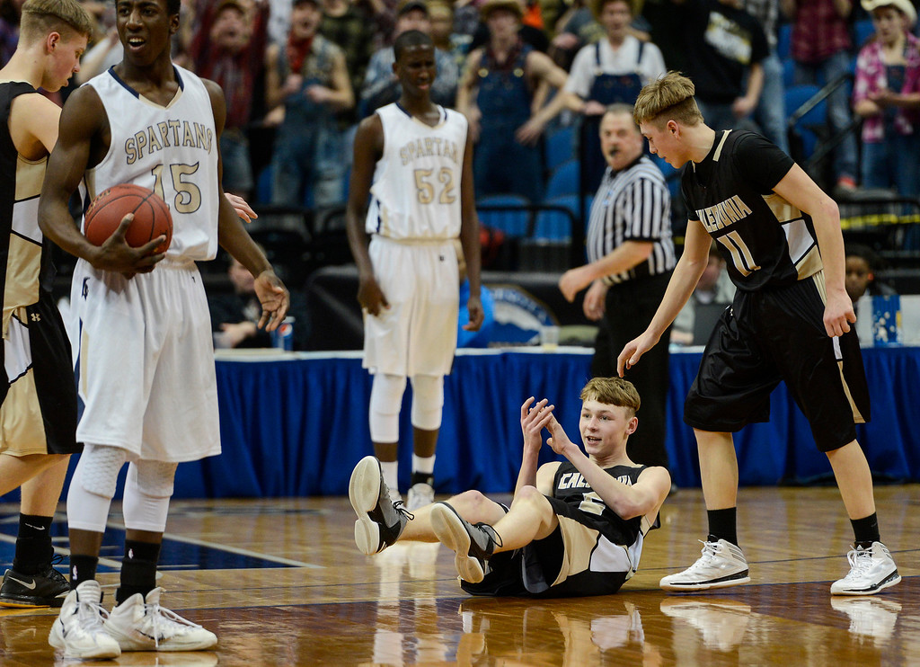 . Caledonia guard Josh Nord, on the floor, is offered a hand up by teammate Colton Lampert, after being fouled by SPA guard Dalante Peyton, left, during the first half. (Special to the Pioneer Press: Matt Mead)