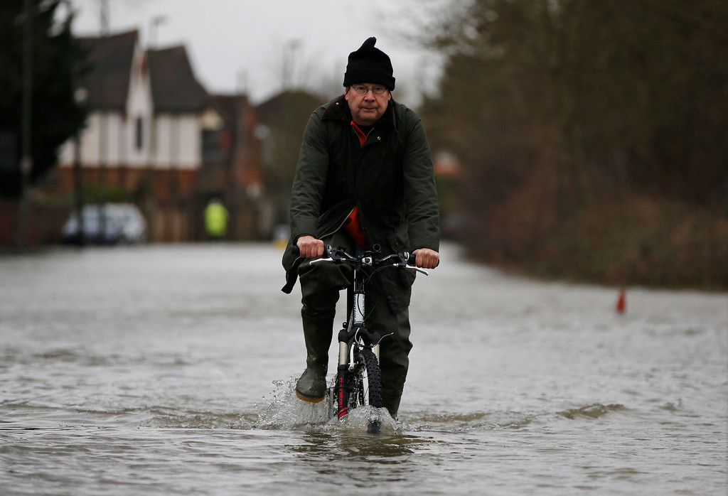 . A local resident cycles through the flooded part of the town of Staines-upon-Thames, England, Wednesday, Feb. 12, 2014. (AP Photo/Lefteris Pitarakis)