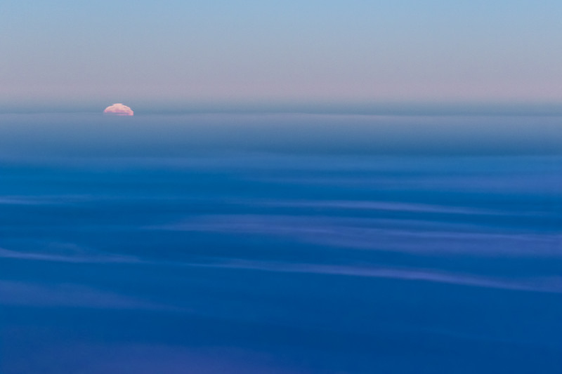 The full moon starts to rise above a bank of clouds in an aerial photo