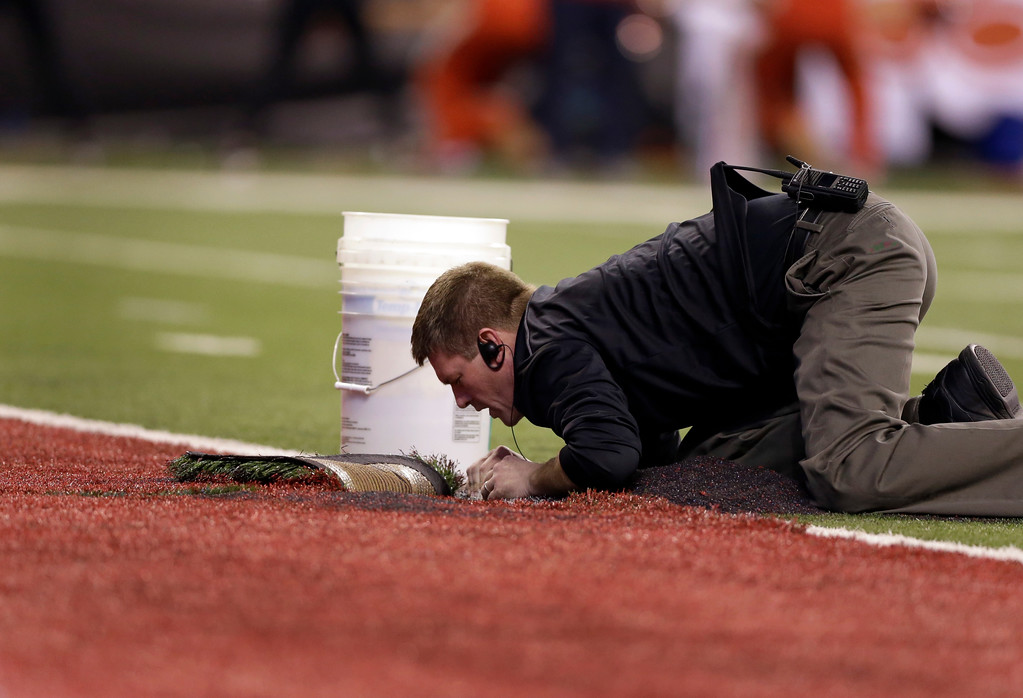 . A worker repairs the artificial turf during the second half of the Big Ten championship NCAA college football game between Ohio State and Wisconsin, Saturday, Dec. 2, 2017, in Indianapolis. (AP Photo/AJ Mast)