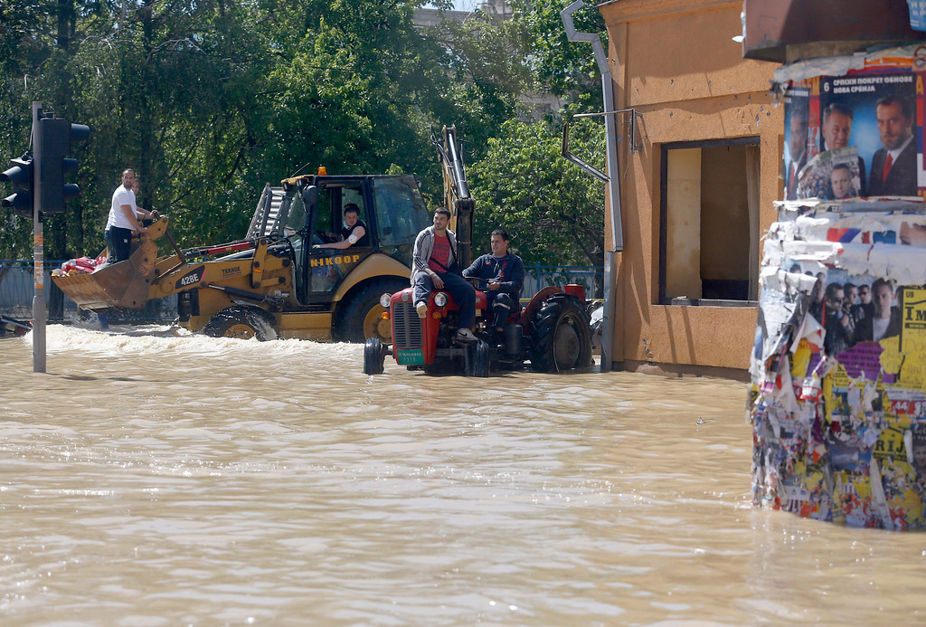 . People drive a tractor and bulldozer in a flooded street in Obrenovac, some 30 kilometers (18 miles) southwest of Belgrade, Serbia, Monday, May 19, 2014. Belgrade braced for a river surge Monday that threatened to inundate Serbia\'s main power plant and cause major power cuts in the crisis-stricken country as the Balkans struggle with the consequences of the worst flooding in southeastern Europe in more than a century. At least 35 people have died in Serbia and Bosnia in the five days of flooding caused by unprecedented torrential rain, laying waste to entire towns and villages and sending tens of thousands of people out of their homes, authorities said. (AP Photo/Darko Vojinovic)
