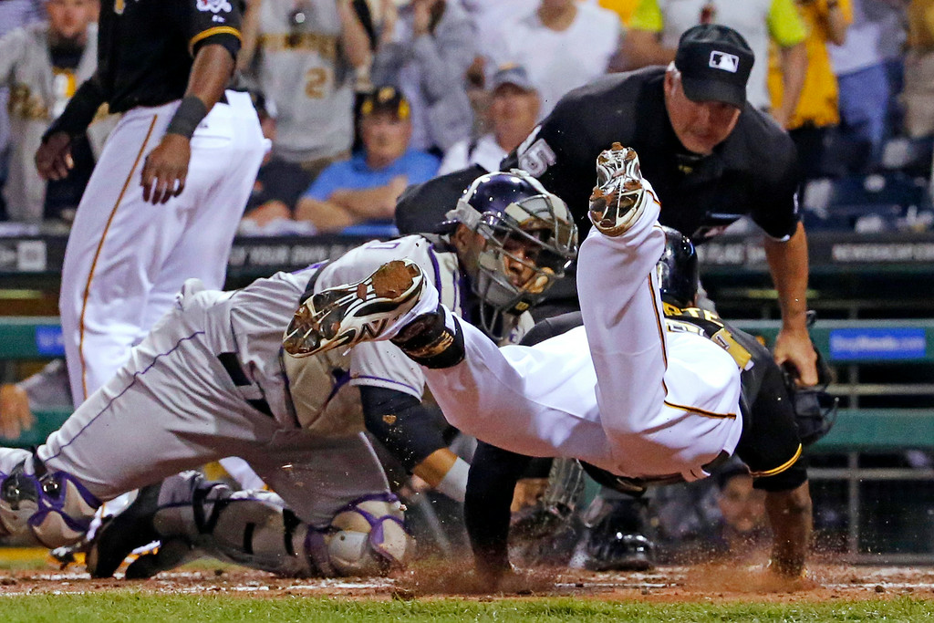 . Pittsburgh Pirates\' Starling Marte, right, slides into the tag by Colorado Rockies catcher Wilin Rosario, center, as umpire Tim Timmons watches during the fifth inning of a baseball game in Pittsburgh on Friday, July 18, 2014. Marte attempted to stretch a triple into an inside-the-park home run and was out at the plate, but not before driving in Gregory Polanco with the Pirates\' first run. (AP Photo/Gene J. Puskar)