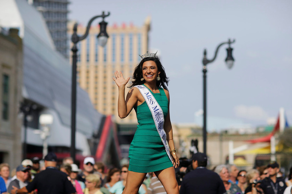 . Miss Massachusetts Amanda Narciso waves as she walks on a runway as Miss America contestants arrive in Atlantic City, N.J. on Tuesday, Sept. 3, 2013. The Miss America pageant is back in the city where it began, six years after spurning the city for Las Vegas. The pageant held a welcoming ceremony Tuesday for the 53 contestants, one from each state plus the District of Columbia, Puerto Rico and the U.S. Virgin n Islands. The contestants filed out of Boardwalk Hall, where the competition will begin next week and culminate days later, and walked across the Boardwalk to a stage. (AP Photo/Mel Evans)
