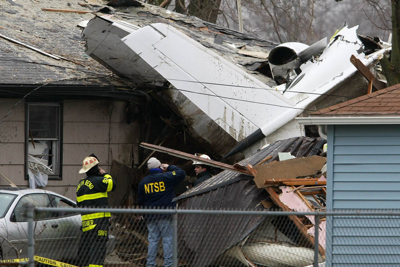 . A National Transportation Safety Board investigator and South Bend firefighters survey, early Monday, March 18, 2013, the scene of Sunday\'s fatal plane crash, along Iowa Street in South Bend, Ind. (AP Photo/South Bend Tribune, James Brosher)