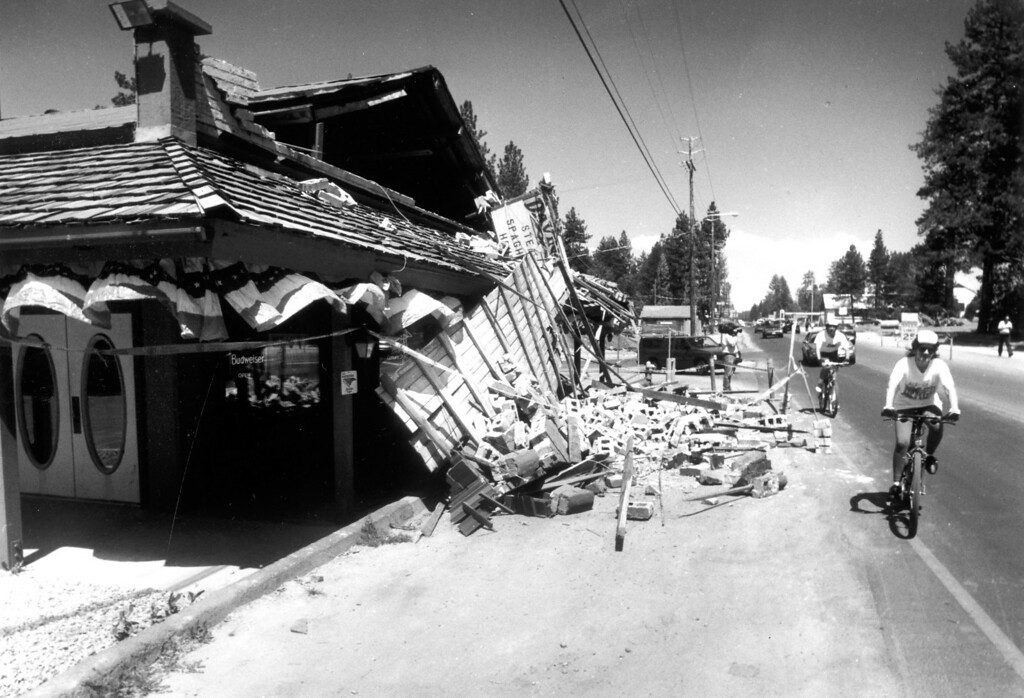 . June 28, 1992: Bicyclists ride by Davino\'s Spaghetti and Steak House in Big Bear, which was one of many local structures damaged by Sunday\'s quake.  Daily News file photo