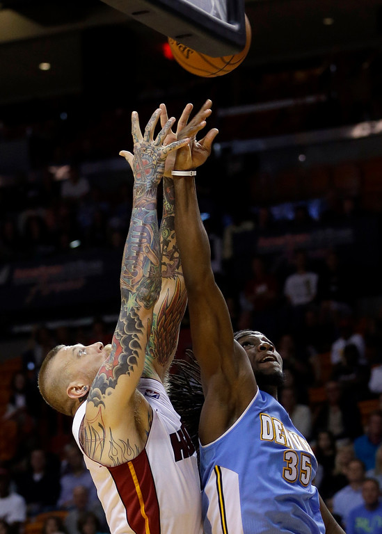 . Miami Heat forward Chris Andersen, left, battles Denver Nuggets forward Kenneth Faried (35) for control of a rebound during the second half of an NBA basketball game in Miami, Friday, March 14, 2014. The Nuggets won 111-107. (AP Photo/Alan Diaz)