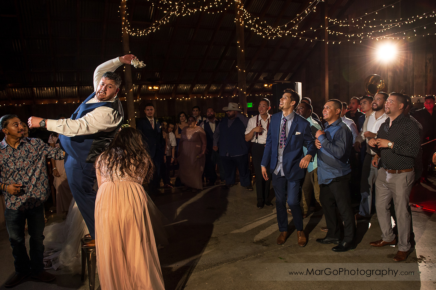 groom tossing garter during mexican wedding reception at Taber Ranch Vineyards