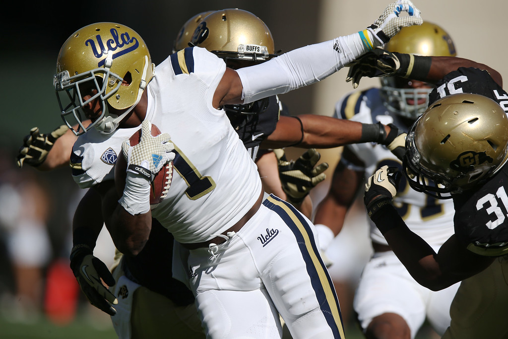 . UCLA punt returner Ishmael Adams, left, breaks away for short gain from Colorado special teams player Kenneth Olugdobe in the first quarter of an NCAA football game in Boulder, Colo., on Saturday, Oct. 25, 2014. (AP Photo/David Zalubowski)