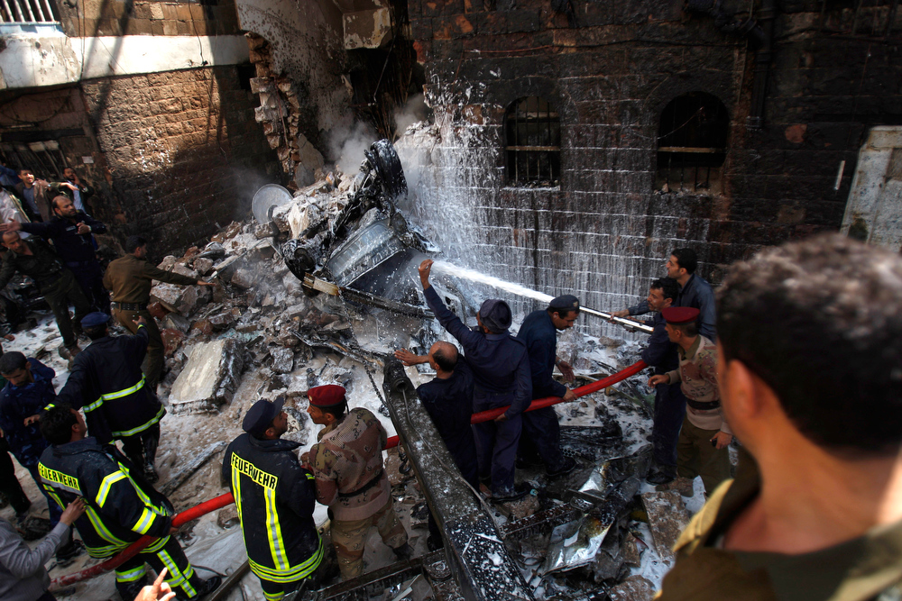 . A Yemeni soldier, right, looks at soldiers and fire fighters working to extinguish fire at the site of a plane crash in Sanaa, Yemen, Tuesday, Feb. 19, 2013. A Yemeni official says a military plane on a training exercise crashed into a neighborhood in the country\'s capital, Sanaa, killing and injuring scores of people. (AP Photo/Hani Mohammed)