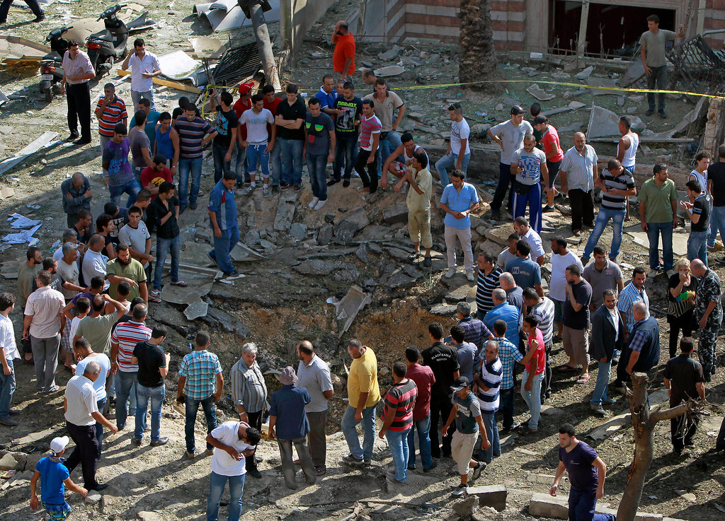 . Lebanese people stand next to a blast crater outside Salam Mosque, in the northern city of Tripoli, Lebanon, Friday Aug. 23, 2013.  (AP Photo/Bilal Hussein)