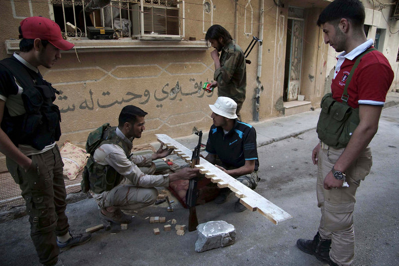 . A Free Syrian Army fighter puts his weapon on a handmade wooden weapons holder on a street in Deir al-Zor April 20, 2013. Picture taken April 20, 2013. REUTERS/Khalil Ashawi