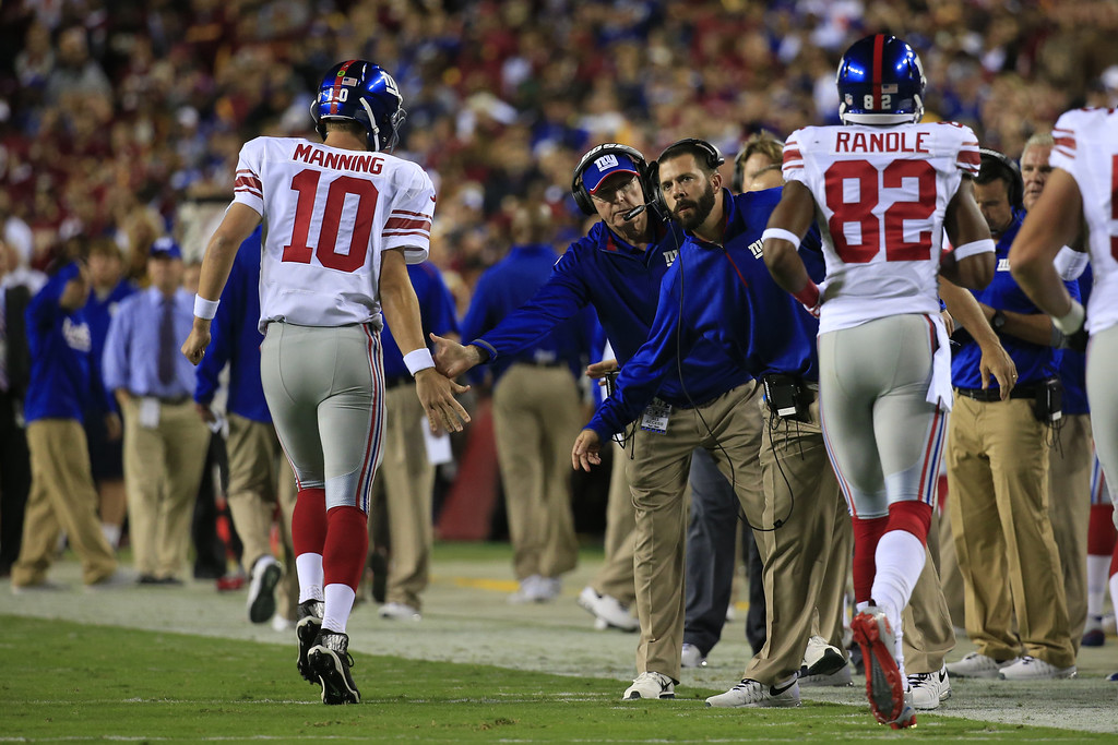 . LANDOVER, MD - SEPTEMBER 25:  Quarterback Eli Manning #10 of the New York Giants is congratulated by head coach Tom Coughlin during a game against the Washington Redskins at FedExField on September 25, 2014 in Landover, Maryland. (Photo by Rob Carr/Getty Images)