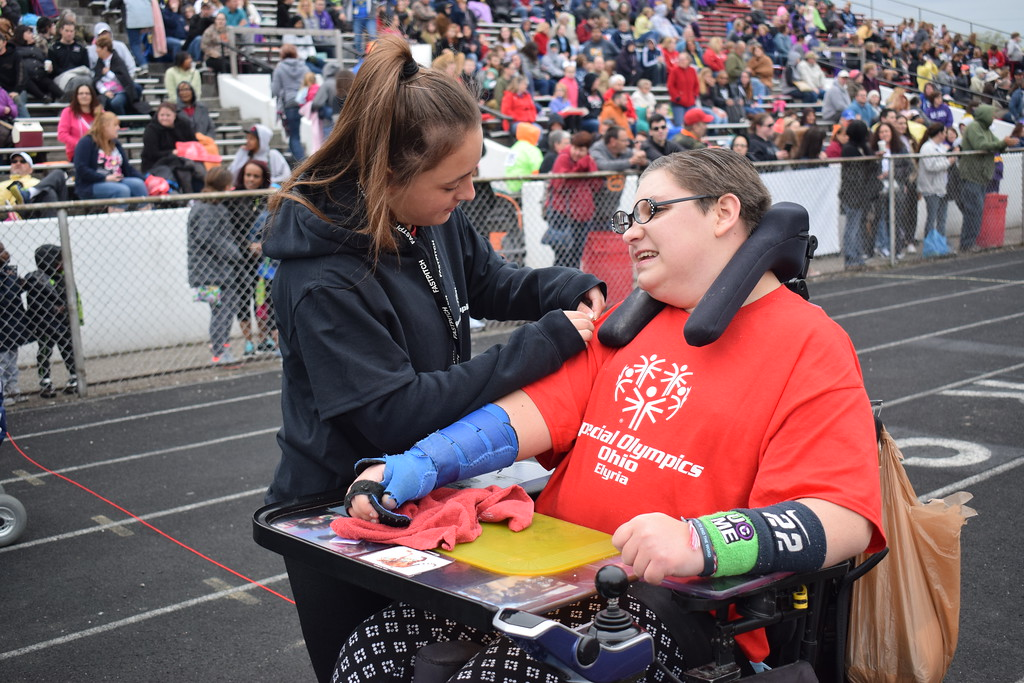 . Briana Contreras � The Morning Journal <br> Elyria High School\'s Mallory Phares, sophomore, pins a ribbon onto her classmate Ally Norris, junior, after winning the 30 Meter Motorized Wheelchair Race at the 38th Annual Lorain County Special Olympics Track and Field Event held on May 11 at Ely Stadium in Elyria.