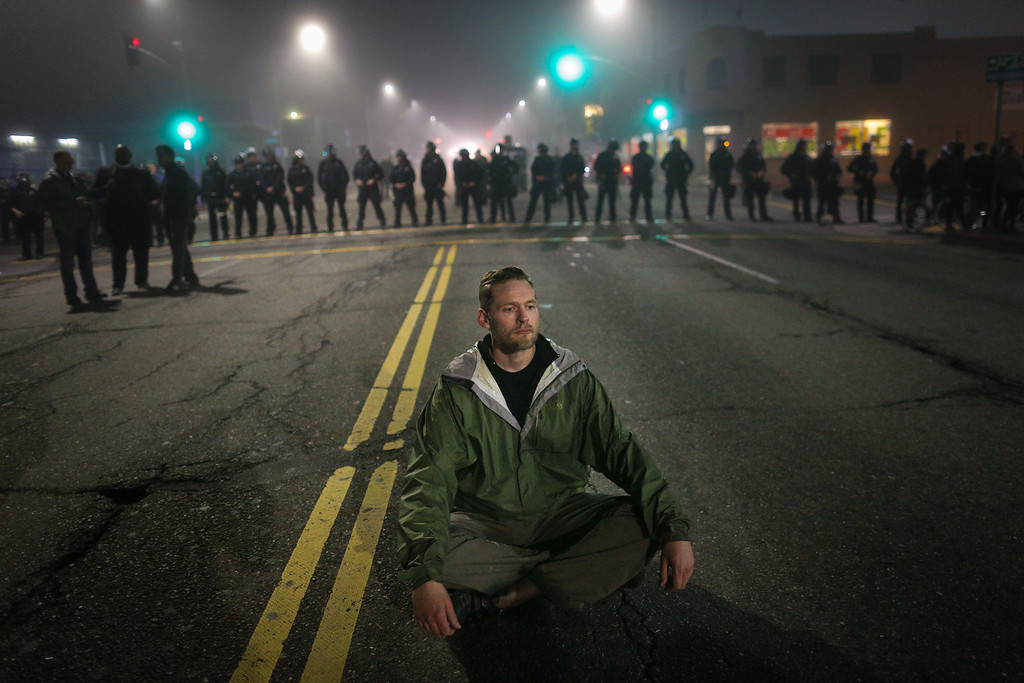 . A man who identified himself as Mike V. sits in the street after being blocked by a line of police officers on the second night of demonstrations following a Staten Island, New York grand jury\'s decision not to indict a police officer in the chokehold death of Eric Garner on December 4, 2014 in Oakland, California. The grand jury declined to indict New York City Police Officer Daniel Pantaleo in Garner\'s death. (Photo by Elijah Nouvelage/Getty Images)