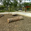log seats and circular timber pallet seating with water play and post and rail shade structure