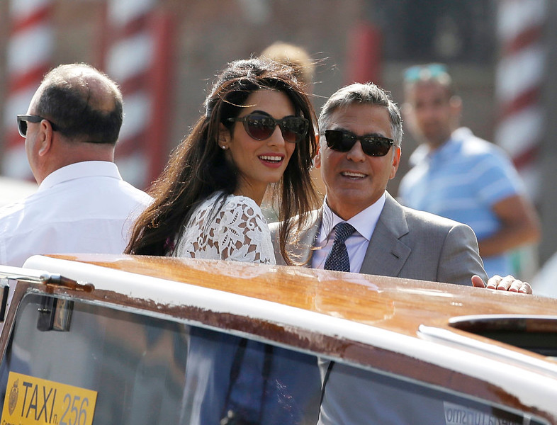 . George Clooney is flanked by his wife Amal Alamuddin as they cruise the Grand Canal after leaving the Aman luxury Hotel in Venice, Italy, Sunday, Sept. 28, 2014. George Clooney married human rights lawyer Amal Alamuddin Saturday, the actor\'s representative said, out of sight of pursuing paparazzi and adoring crowds. (AP Photo/Luca Bruno)