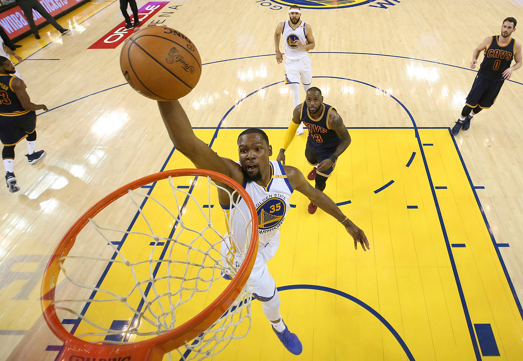 . Golden State Warriors forward Kevin Durant (35) dunks in front of Cleveland Cavaliers forward LeBron James during the first half of Game 1 of basketball\'s NBA Finals in Oakland, Calif., Thursday, June 1, 2017. (Ezra Shaw/Pool Photo via AP)
