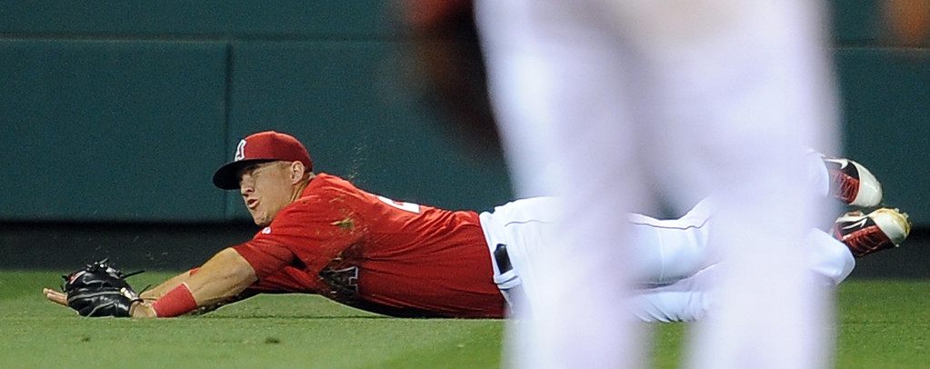 . Los Angeles Angels left fielder Mike Trout dives for a base hit by Los Angeles Dodgers\' Juan Uribe (not pictured) in the second inning of a spring baseball game on Thursday, March 28, 2012 in Anaheim, Calif.   (Keith Birmingham/Pasadena Star-News)